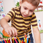 Child  with pencil in play room.