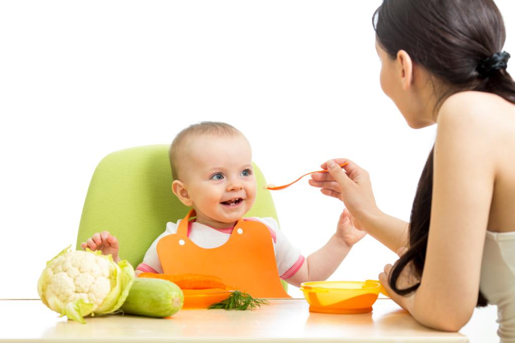 mother feeding baby girl
